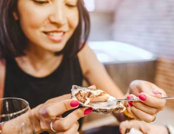 a woman eating oysters at a restaurant
