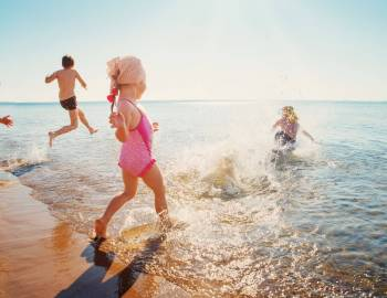 children running into the ocean on the beach fun kids laughter happy