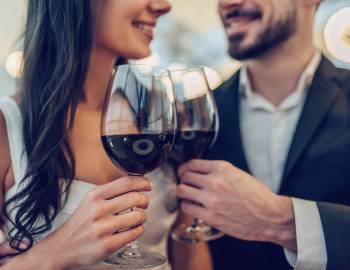 couple cheers with red wine