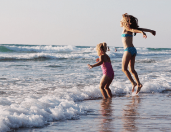Kids in the ocean on the beach
