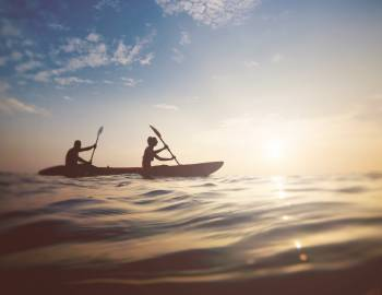 people on boat at sunset kayaking