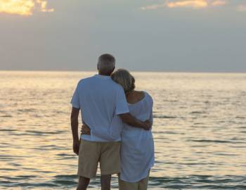 retired couple watching the sunset on the beach