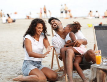 Family on beach smiling and laughing