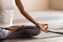 woman meditating and practicing yoga at a studio