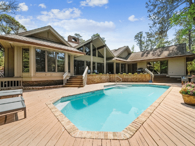 Single family vacation home in front of pool with blue skies.